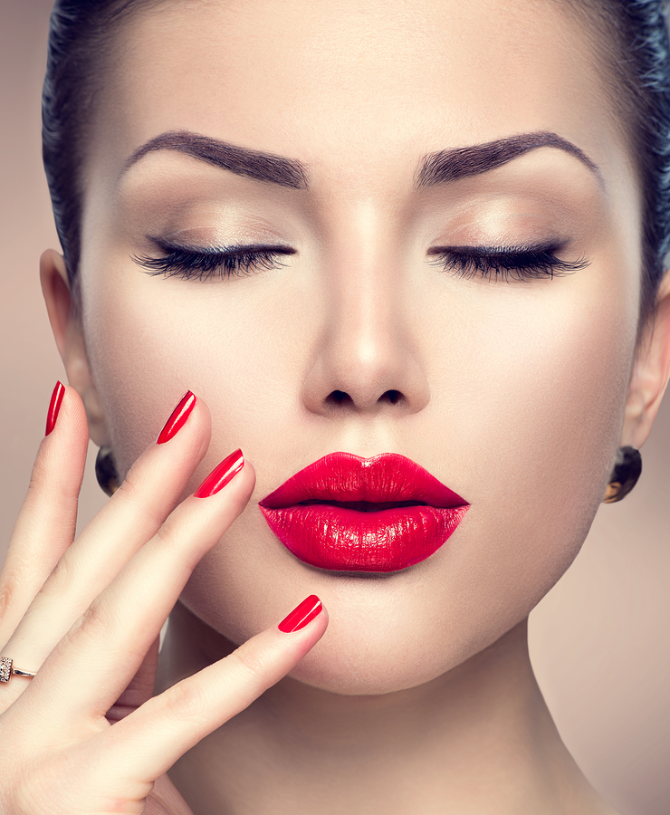 Beautiful model woman with red lipstick, red nails, and long eyelash extensions.